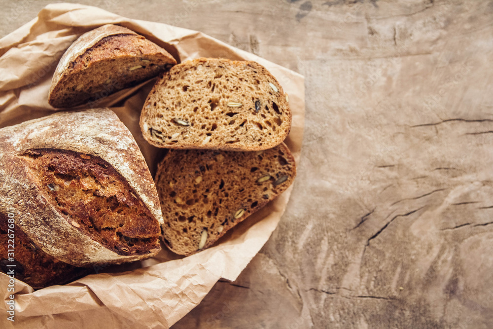 Fototapeta Brown fresh bread with seeds are cut into pieces on old wood background. Copy, empty space for text