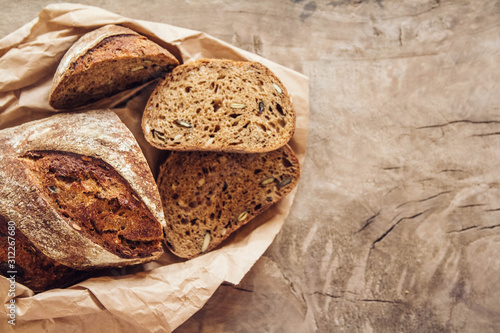 Fototapeta Brown fresh bread with seeds are cut into pieces on old wood background. Copy, empty space for text obraz