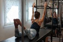Pilates Instructor With A Slim Attractive Body Working Out In Her Studio, Using A Cadillac Reformer.