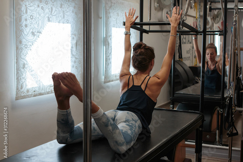 Photo Pilates instructor with a slim attractive body working out in her studio, using a cadillac reformer