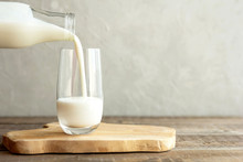 Kefir, Milk Or Turkish Ayran Drink Are Poured Into A Glass Cup From A Bottle. A Glass Stands On A Wooden Stand On A Rustic Wooden Table. Place For Text
