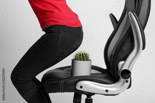 Fotomural Woman sitting down into armchair with cactus on white background, closeup