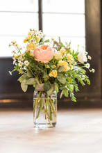 Bouquet Of Flowers In A Glass Vase On Wooden Table