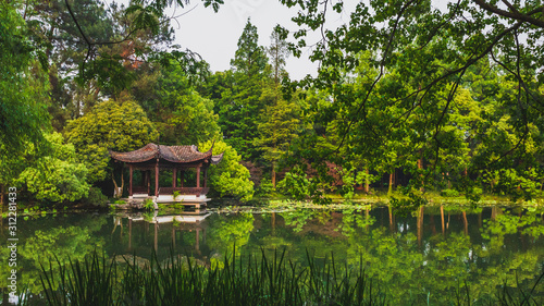 Traditional Chinese architecture by water in park by West Lake, in Hangzhou, Chi Wallpaper Mural