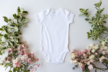 Blank White Baby Grow On An Off White Background With Green Leaves And Pink Roses - Spring Baby Bodysuit Mockup