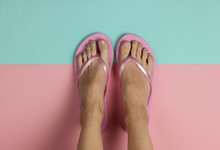 Minimalistic Concept Of Beach Holiday. Female Legs With Flip Flops On A Pink-blue Pastel Background. Top View. Studio Shot