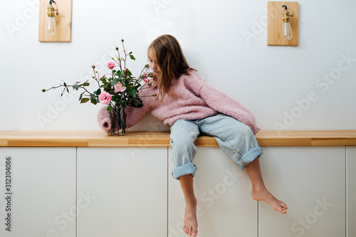 Photo Little barefoot girl in a pink oversized knitted sweater sitting on a shelf in corridor at home, hugging glass jar with roses in it