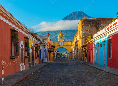 Photo Cityscape of the main street and yellow Santa Catalina arch in the historic city center of Antigua at sunrise with the Agua volcano, Guatemala