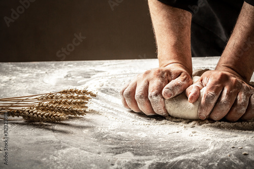 Fototapeta Hands of baker kneading dough isolated on black background