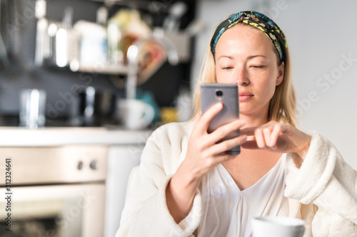 Obraz Beautiful caucasian woman at home, feeling comfortable wearing white bathrobe, taking some time to herself, drinking morning coffee and reading news on mobile phone device in the morning. - fototapety do salonu