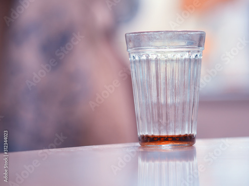 Vászonkép Almost empty glass of alcohol bokeh background