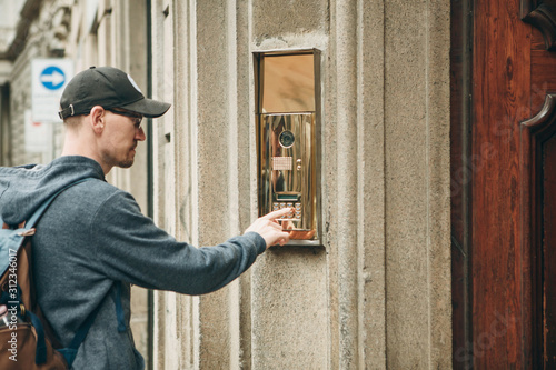 Fotografie, Obraz  A guy or a man or a tourist presses a doorphone button to access inside