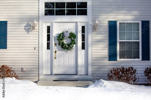 Fototapeta Front of a house  with a Christmas wreath on the front door in winter obraz