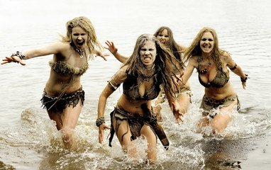 A group of four neanderthal women are on the attack.  They charge through water running and screaming as  they attack.