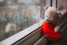 A Toy Pink Sad Bear With A Red...