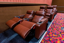 A Recently Renovated Movie Theater Interior With Luxurious Reclining Leather Chairs