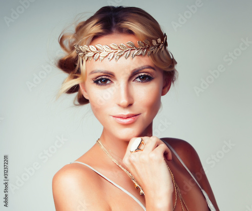 Fotomural young blond woman dressed like ancient greek godess, gold jewelry close up isola