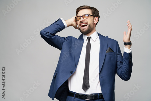 Obraz Very happy successful winner gesturing businessman over grey background - fototapety do salonu