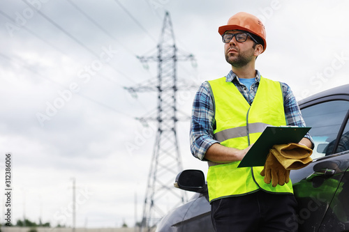 Obraz A man in a helmet and uniform, an electrician in the field. Professional electrician engineer inspects power lines during work. - fototapety do salonu