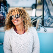 Leinwanddruck Bild - Cheeful and beautiful curly blonde caucasian adult young woman smiling and laughing with sunglasses and blue vintage van in background - concept of happy people