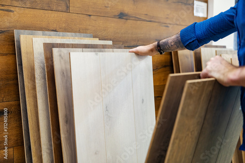 Obraz na plátně man choosing floor laminate for his home in flooring store