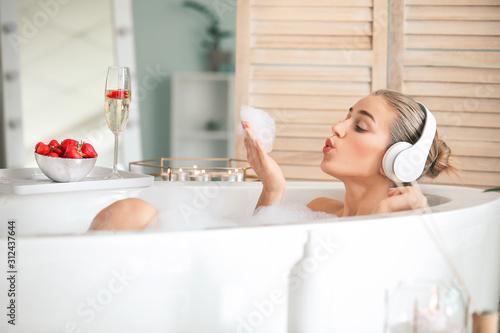 Cuadros en Lienzo Beautiful young woman listening to music in bathroom