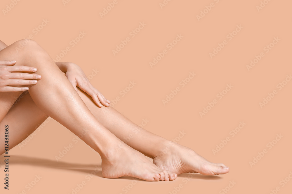 Fototapeta Legs of beautiful young woman on color background