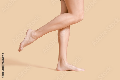Legs of beautiful young woman on color background Wallpaper Mural
