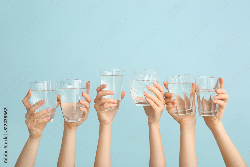 Fotografia Female hands with glasses of water on color background