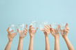 Leinwanddruck Bild - Female hands with glasses of water on color background