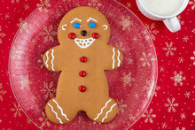 Large Gingerbread Cookie On A Glass Platter, Red Fabric Background With Gold Snowflakes, White Mug With Milk