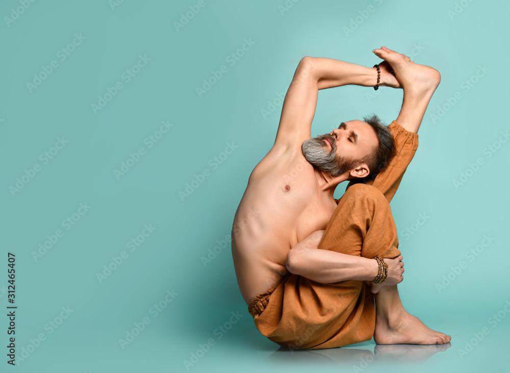 Fototapeta Old man practicing yoga classic asana stretching pose in fitness gym
