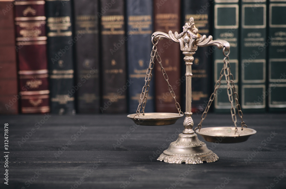 Fototapeta  Scales of Justice on a black wooden background.