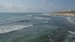 Aerial view from drone of slightly rough sea and cityscape in background