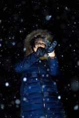 young girl at night in jackets on the background of snowfall