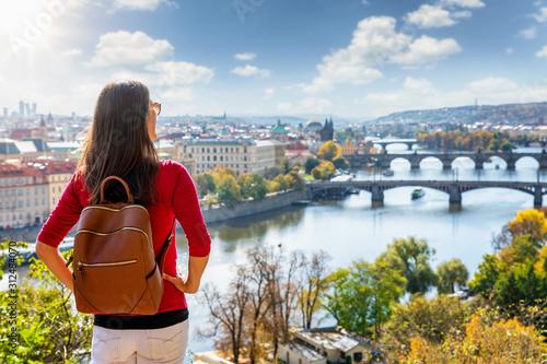 Obraz Eine Reisende Frau mit rucksack genießt die Aussicht über die Stadt Prag in Tschechien während eines sonnigen Herbsttages - fototapety do salonu