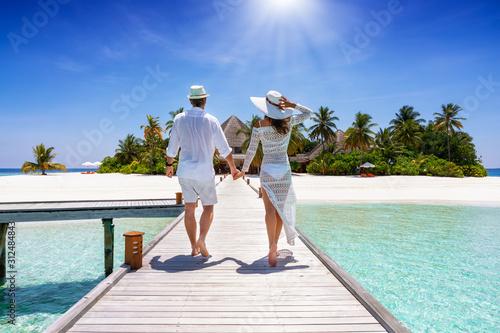 Ein glückliches Paar im Urlaub läuft händehaltend über einen Steg auf eine tropi Canvas Print