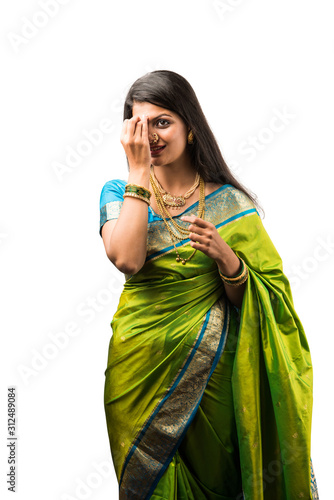 Indian beautiful lady in green saree getting ready for festival of auspicious occasion, wearing gold jewellery, Standing isolated over white background Fototapet
