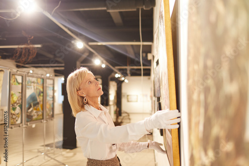 Obraz na plátne Wide angle portrait of elegant mature woman hanging paintings while working in a