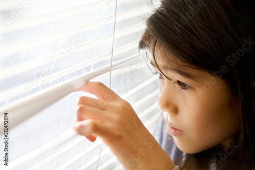 Little Asian girl cautiously peeking out window through blinds Canvas Print