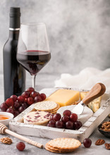 Glass And Bottle Of Red Wine With Selection Of Various Cheese In Wooden Box And Grapes On Light Table Background. Blue Stilton, Red Leicester And Brie Cheese With Cheddar And Nuts With Honey.
