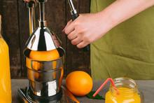 Woman Using Orange Juicer Apparatus At Home
