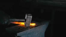 Forge Workshop. Smithy Manual Production. Hands Of Smith With Hammer Hit On Glowing Hot Metal, On The Anvil, The Forging Process. Blacksmith Makes Iron Products For Manufacture Of Fireplace, Stove.