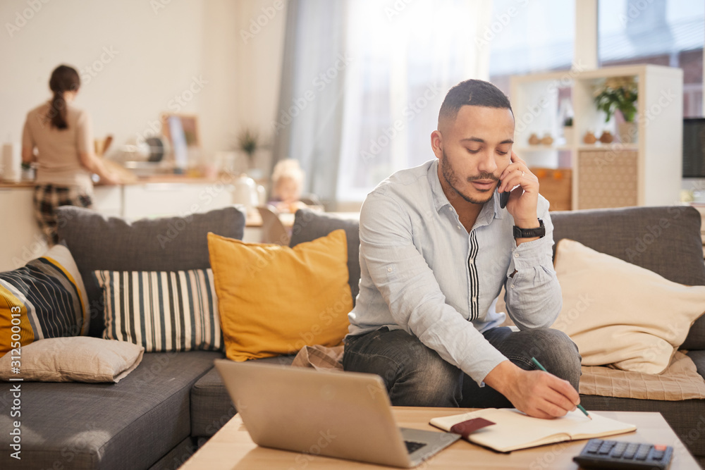 Fototapeta Portrait of modern mixed race man speaking by phone while working from home in cozy interior, copy space