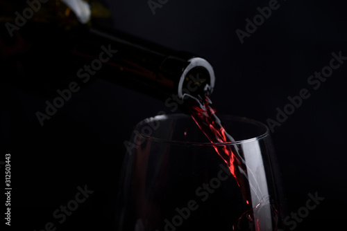 Cuadros en Lienzo Red wine pouring in wine glass over black background