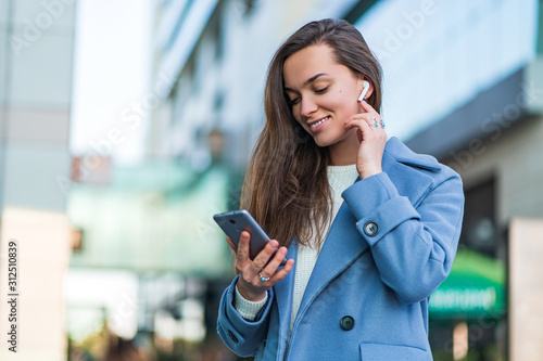 Stylish trendy happy joyful brunette woman in a blue coat holds a smartphone and using wireless white headphones for listen music in the city centre. Modern people - 312510839