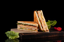 Freshly Made Club-sandwiches Served On A Wooden Chopping Board.