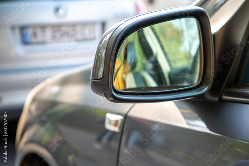 Fototapeta Close up of rearview mirror of a car parked near curb on the side of the street on a parking lot. obraz