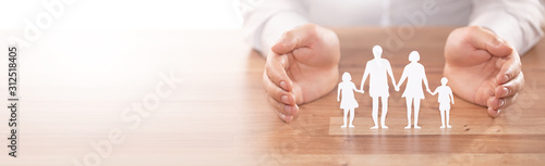 Fotografia  Family care concept. Hands with paper silhouette on table.