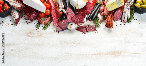 Fotografía Assortment of cheese, dried salami and smoked sausages on a white wooden background